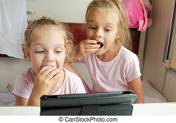 Sisters eating and looking at the tablet in the train - Two...