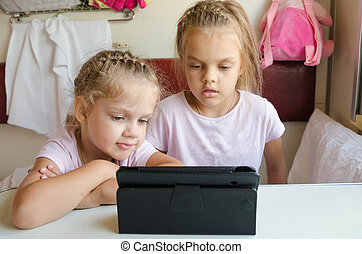 Two girls looking at the tablet in the train - Two girls...