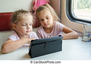 Two girls on a train watching a cartoon in the plate - Two...