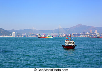 Boats in Hong Kong harbor and Stonecutters bridge