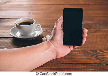 man hand holding a phone with isolated screen  on the wooden background with cup of coffee