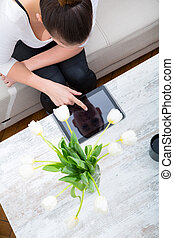Young woman with a Tablet PC on the Sofa - A young woman...