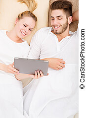 Young couple with a tablet PC in bed - A young and happy...