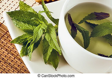 cup of mint tea and fresh leaves