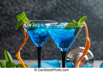 Blue cocktail with ice and mint in martini glasses on gray...