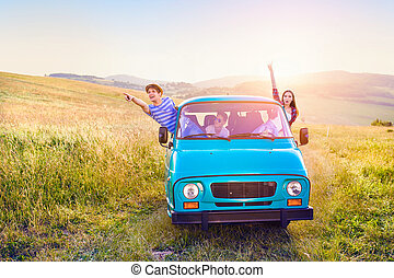 Young frieds leaning out of campervan, green sunny nature -...