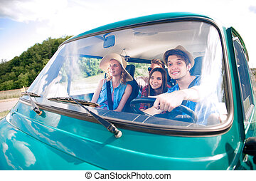 Hipster boy driving an old campervan with teenagers,...