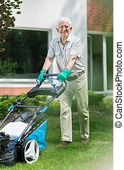 Caring about your lawn - Senior man is going outside to mown...