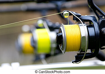 Fishing reels - Close up of three fishing rods mounted on...