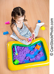 Child girl sculpts from kinetic sand in play room....