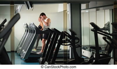 A men and a girl running on the treadmill at the gym - the...