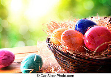 Easter eggs on a wooden table in nature elevated view -...