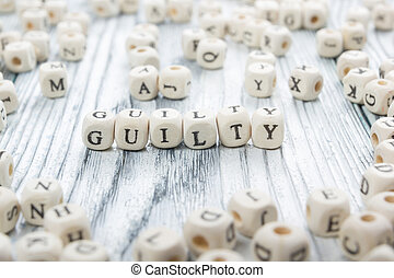 guilty word written on wood block Wooden Abc