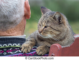 Cat on mans shoulder - Rear view od senior man sitting on...