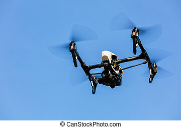 Drone flying against blue sky background - Drone with...