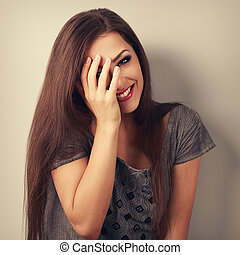 Happy laughing brunette young woman cover the hand her face...
