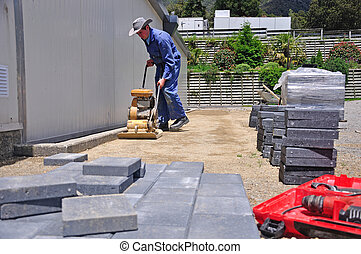 setting out the pavers - Builder using a vibrating roller...