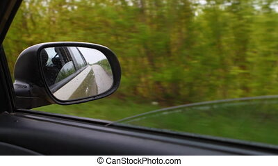 reflected in the side mirror of a car traveling