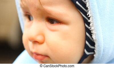 a little sad child looks around, close-up