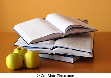 three green apples and four opened books on the desk