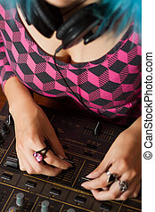 Mixing with faders - Hip young girl DJ mixing music on a...