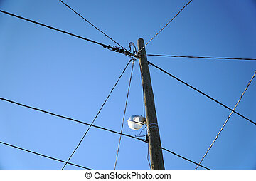pole with wires on blue sky - a pole with wires on blue sky