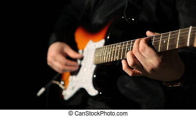 guitarist playing guitar on a black background