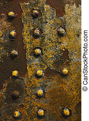 grunge background of rusty rivetted metal - a yellow painted...