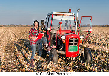 Woman with tractor on the field - Young farmer girl standing...