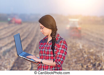 Woman with laptop in corn field - Young woman agronomist...
