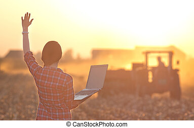 Woman with laptop and tractor - Young woman with laptop...