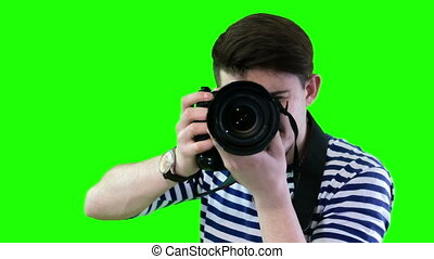 A man in a striped sweater with a camera taking pictures...