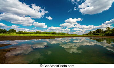 time lapse with running clouds with reflection in water and deep blue sky