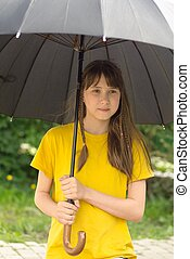 girl under an umbrella during a storm in the park