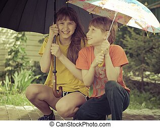 girl and boy  under an umbrella during a storm in the park