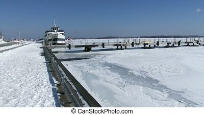 Boat docked on frozen lake Ontario - Boat docked in Toronto,...
