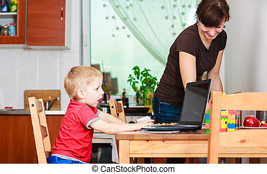 Little boy with laptop and mother cleaning - Technology and...