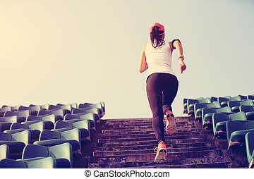 Runner athlete running on stairs woman fitness jogging...