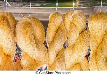 Golden raw silk is hanging for ready to made a silk