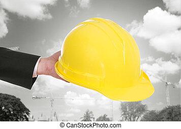 hand of engineer holding helmet with construction crane...