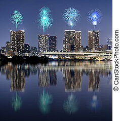 Fireworks celebrating over Tokyo cityscape with mirror...