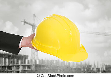 hand of engineer holding helmet with construction crane...