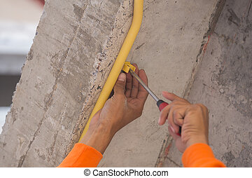 worker install PVC pipes for electric conduit - hand of...