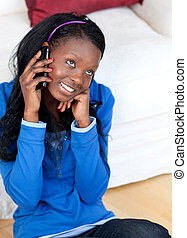 Pretty young woman talking on phone sitting on the floor