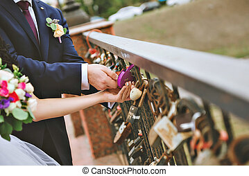 The decorative lock in hands of newlyweds, Space for text on lock. Wedding Bouquet on background