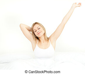 Glowing woman stretching while getting up in the morning