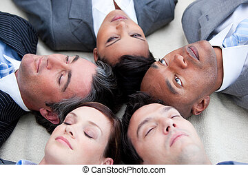 Close-up of relaxed business team lying in circle on the...