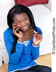 Attractive woman talking on phone in the living-room