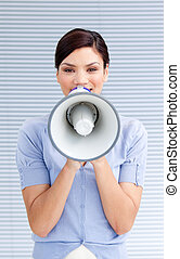 Positive businesswoman yelling through a megaphone at work