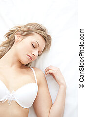 Asleep woman in underwear lying on bed at home
